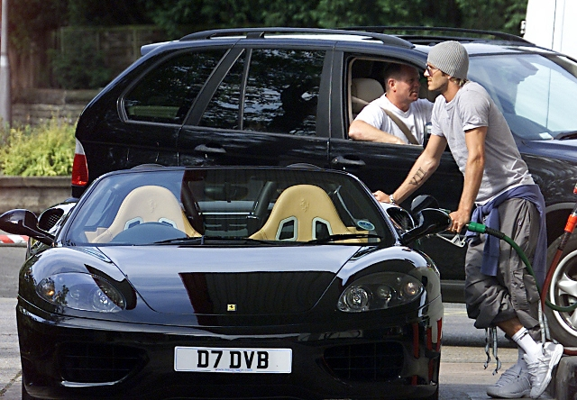 PICS BY JAMES CLARKE 07971 879251 MAN UTD AND ENGLAND CAPTAIN DAVID BECKHAM TAKES A GOOD 5 MINUTES FILLING THE TANK ON HIS FERRARI 360 SPIDER AT THE HIS LOCAL PETROL STATION IN ALDERLEY EDGE CHESHIRE.